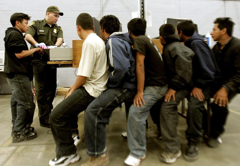 Policajt odoberá odtlačky prstov migrantov v americkom meste Nogales. FOTO – SITA/AP