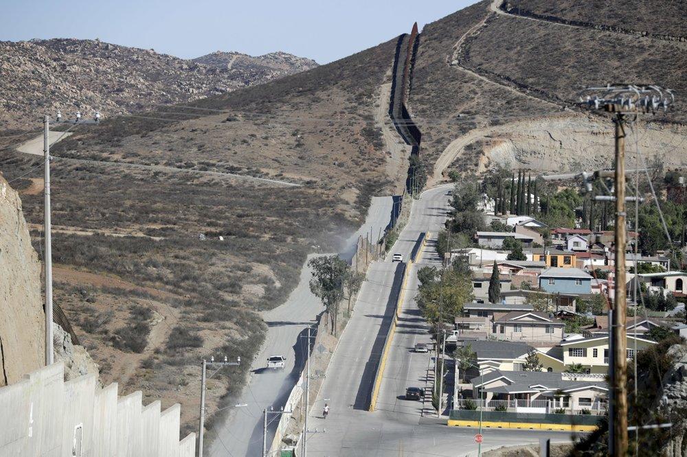 Na snímke pohľad z mexického mesta Tecata na auto pohraničnej stráže, ktoré jazdí pozdĺž kovového plotu pozdĺž mexicko-americkej hranice. FOTO - TASR/AP