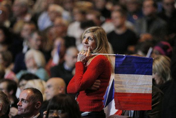 Podporovateľka počúva Juppého príhovor na predvolebnom mítingu v Paríži.