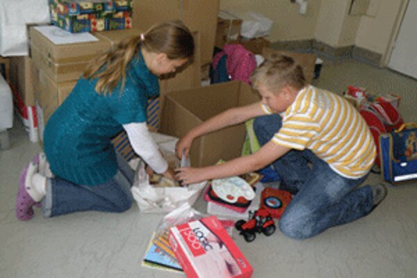 Do rozbaľovania balíkov, ktoré na hornú Nitru poslali deti z Bratislavy, sa pustili aj Tereza z Adriánom.