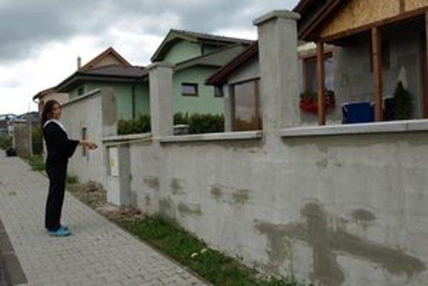 Tatiana Krausková ukazuje, že niektoré múry plota sú vyššie, iné nižšie.