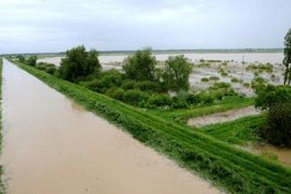 Vľavo naplnená riečka Trnávka, ktorej hrádza zadržiava vyliatu vodu z pretrhnutej hrádze na Ondave.