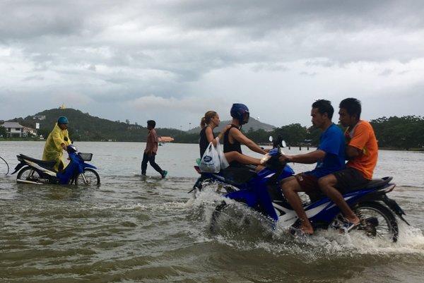Thajčania cestujú po ceste, na ktorú sa vylialo neďaleké jazero.