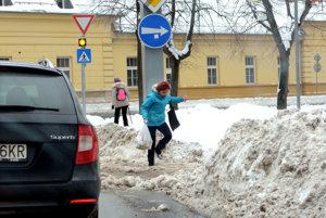 Moyzesova ulica. Snehové mantinely popri cestách a kaša na chodníkoch poriadne brnkajú chodcom na nervy.