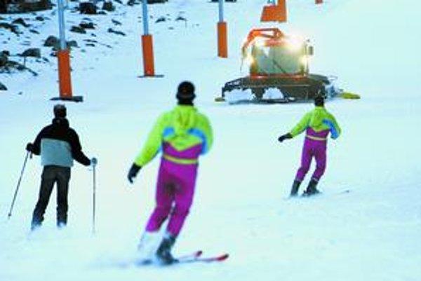 Na zjazdovke jazdia lyžiari popri ratraku naďalej.