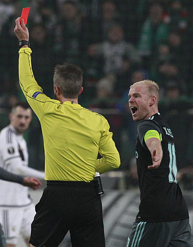Kapitán Ajaxu Amsterdam Davy Klaassen (vpravo) sa háda s rozhodcom po tom, ako ukázal červenú kartu jeho spoluhráčovi Kennymu Tetemu.