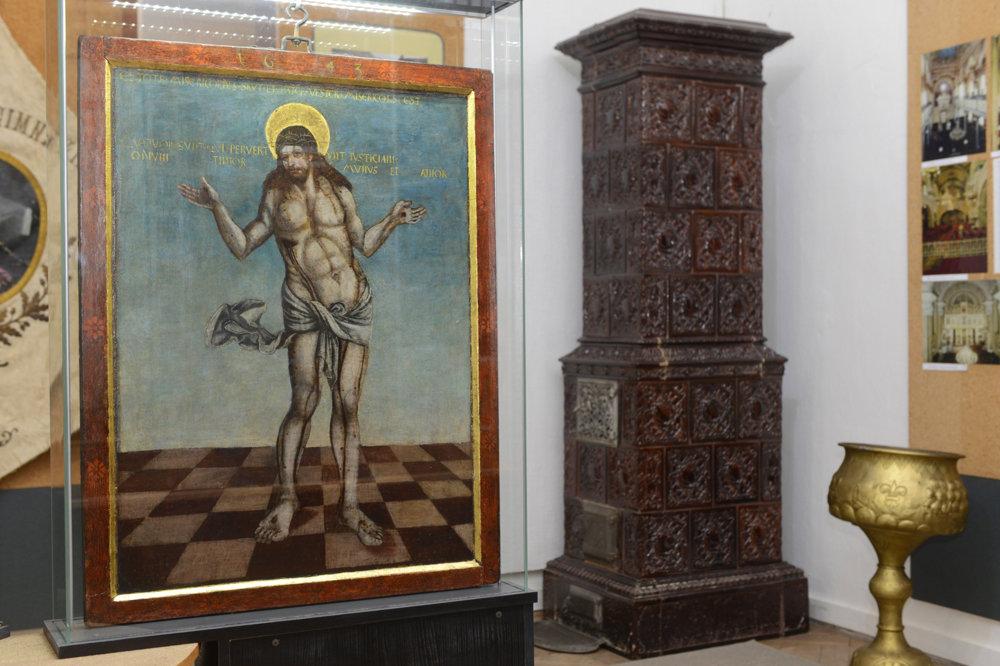 Obraz Muž bolesti – víťaz nad smrťou z obojstrannej tabuľovej maľby z roku okolo 1530, premaľovná v roku 1643. Vpravo v pozadí kachľová pec z 19. storočia, výrobok prešovskej kachliarne,