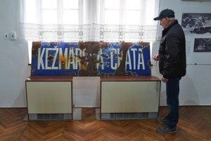 Muž si prezerá kovovú tabuľu z bývalej Kežmarskej chaty počas výstavy.
