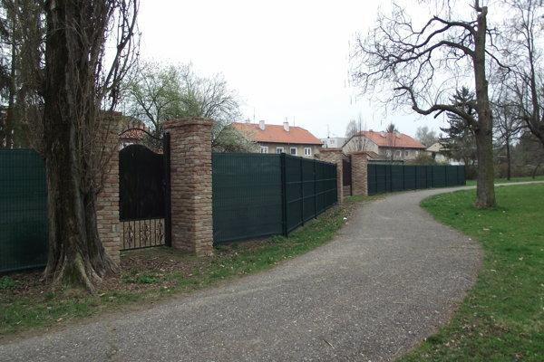 Plot v mestskom parku. Nachádza sa za ním trávnik, ktorý bol predtým verejný. Pozemok patrí cirkvi.