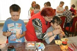 Ľudmila Bátorová pomáha deťom pri voskovaní kraslíc.