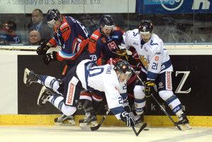 Dvaja slovenskí hokejisti Michal Čajkovský (vľavo) a Libor Hudáček bojujú pri mantineli o puk s dvojicou hráčov Fínska.