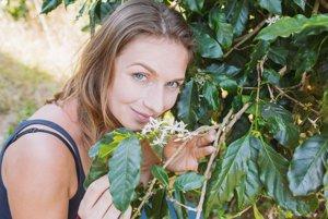 Anka Ribovičová pri kvitnúcom kávovníku.