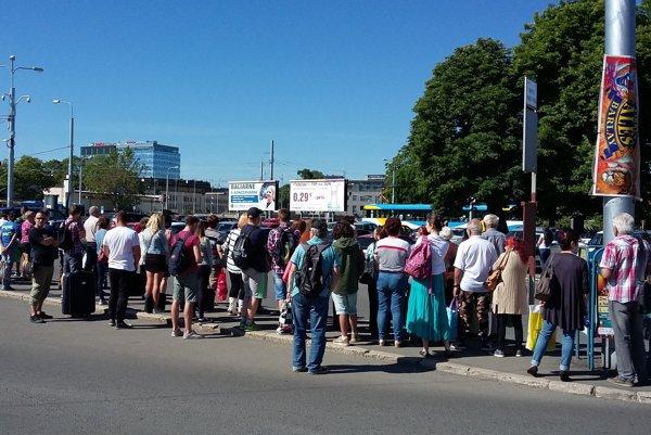 Preplnený ostrovček. Niektorí cestujúci čakali na autobus postávaním na ceste.