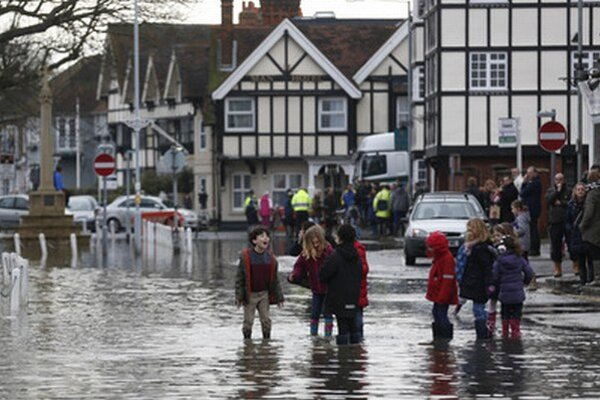 Deti stoja na zaplavenej ulici britského mesta Datchet.
