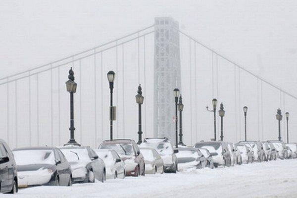 Autá pokryté snehom pred mostom Georga Washingtona v New Yorku.