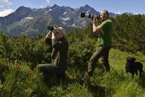 Lesník z Ochranného obvodu Tatranská Javorina Marcel Tobis vyhľadával kamzíky pomocou fotoaparátu s teleobjektívom, vľavo Igor Stavný zo ŠL TANAPu z Tatranskej Lomnice pozoruje terén pomocou ďalekohľadu.