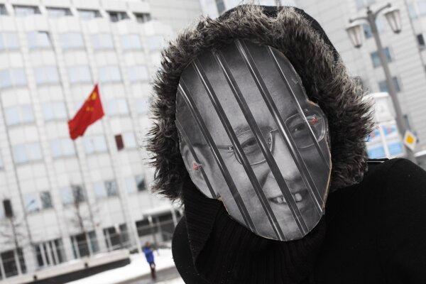 Demonštrant , ktorý má na tvári podobizeň laureáta Nobelovej ceny mieru za rok 2010 Číňana  Liou Siao-poa protestuje pred budovou čínskeho veľvyslanectva v Berlíne.