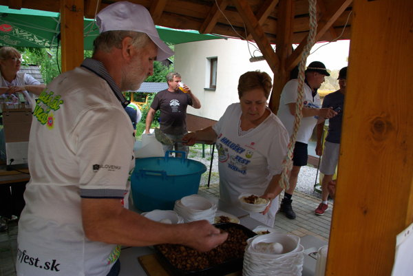 Zakladateľ podujatia Svetlan Turčan pomáha so servírovaním halušiek pre návštevníkov.