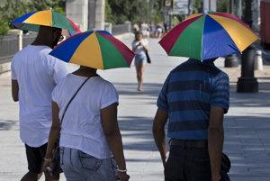 Turisti v Madride sa chránia pred slnkom.