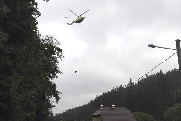 Pri osádzaní nových betónových stĺpov v kopcovitom teréne pomáhal aj vrtuľník.