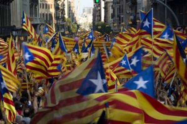 Demonštranti mávajú katalánskymi vlajkami.