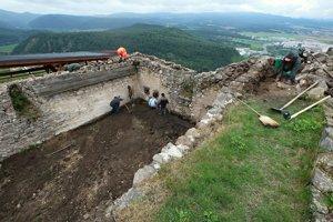 Čistenie zásypu koruny múrov paláca na Hornom hrade pred ich sanáciou a reštaurovaním omietok.