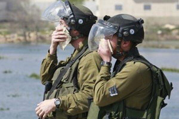 Izraelskí vojaci sa pri proteste v osade chránia pred slzotvorným plynom.