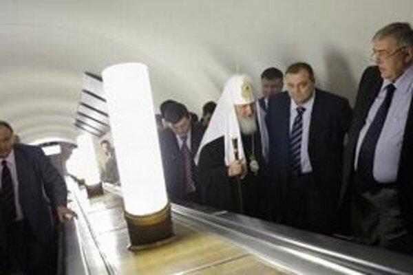 Ruský pravoslávny patriarcha Kirill (tretí sprava) stojí na elektrických schodíkoch po celebrovaní špeciálnej svätej omše na mieste samovražedného bombového výbuchu na stanici metra.