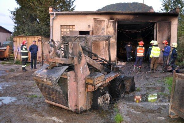 Zhorený nakladač vytiahli stojí pred zhorenou dielňou.
