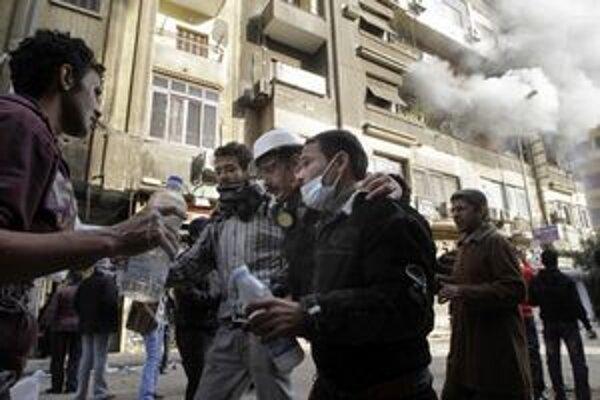 Egyptskí demonštranti pomáhajú zranenému novinárovi Maher Malakovi z námestia Tahrír v Káhire.