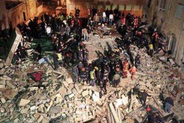 Záchranári v troskách zrútenej budovy.