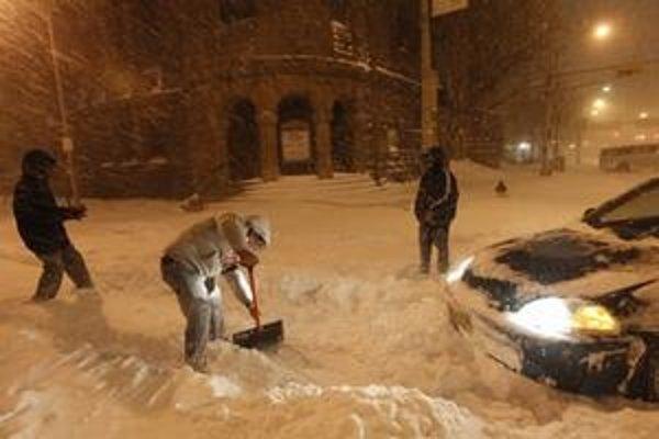 Američan odpratáva sneh pred svojím autom na zasneženej ceste.