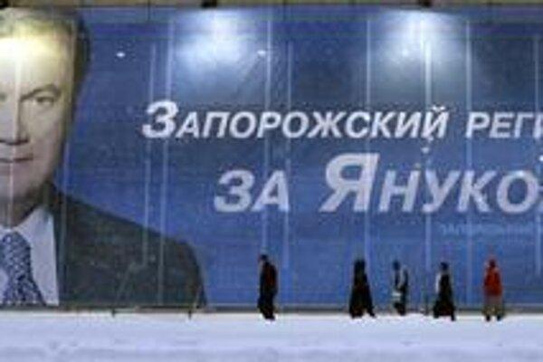 Záporožský región stojí za Janukovyčom, hlása predvolebný bilbord, pred ktorým kráčajú v snehu ľudia. Vo východnej časti Ukrajiny víťazí bývalý premiér, kým západ zasa fandí Tymošenkovej.
