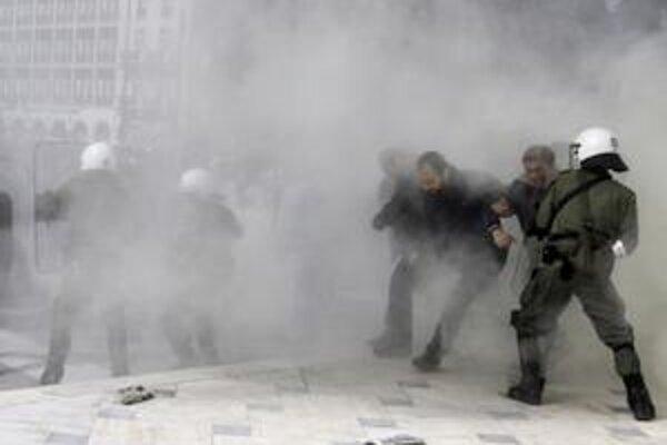 Policajti používajú proti demonštrantom slzotvorný plyn pri hrobe neznámeho vojaka pred budovou parlamentu v centre Atén.