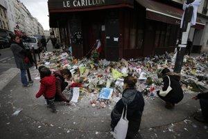 Ľudia kladú kvety a zapaľujú sviečky pred reštauráciou La Carillon, jedným z miest teroristických útokov v Paríži, fotografia je z 16. novembra 2015.