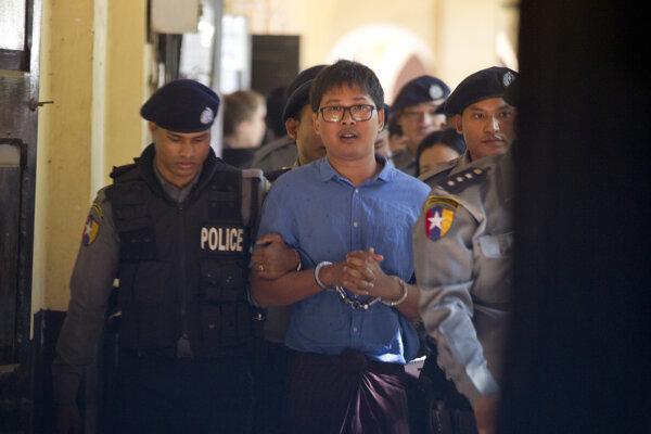 Novinár Reuters Wa Lone (v strede) po zadržaní barmskou políciou.