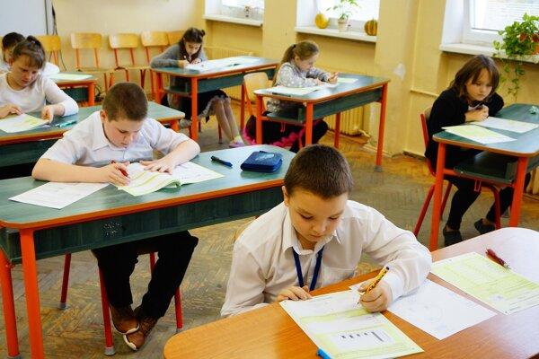 Piataci vypĺňajú test z matematiky počas testovania piatakov známeho ako monitor.