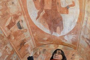 Na snímke farárka Timea Krchová ukazuje na gotické fresky v kostole Reformovanej kresťanskej cirkvi na Slovensku.