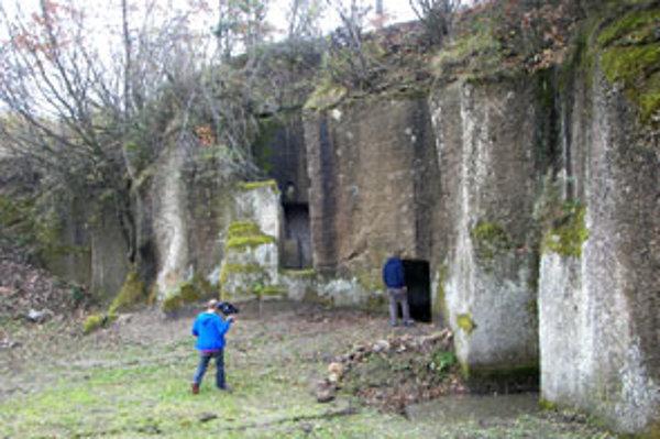 Mladík stojí pri vstupe do kamennej izby.