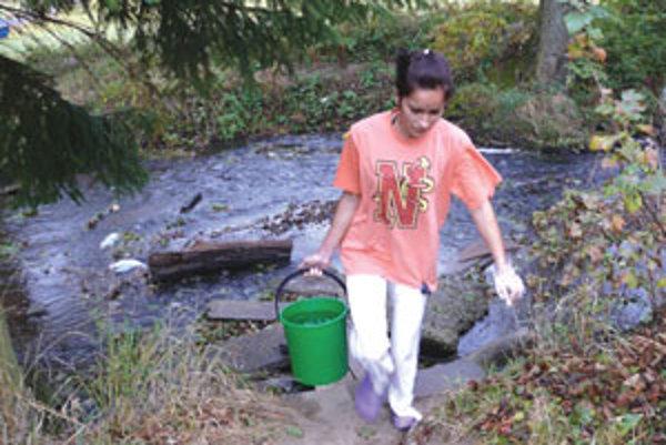 Ľudia si pre vodu chodia do potoka.