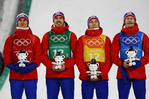 Nórski skokani na lyžiach v zložení zľava Daniel Andre Tande, Andreas Stjernen, Johann Andre Forfang a Robert Johansson oslavujú po víťazstve a zisku zlatej medaily v súťaži družstiev na veľkom mostíku v skokoch na lyžiach.