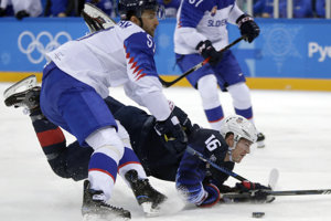 Americký hokejista Ryan Donato (16), padá v súboji o puk s Dominikom Graňákom.