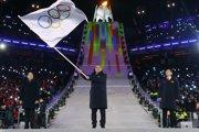 Prezident Medzinárodného olympijského výboru (MOV) Thomas Bach (uprostred) máva olympijskou zástavou počas záverečného ceremoniálu na ZOH 2018.