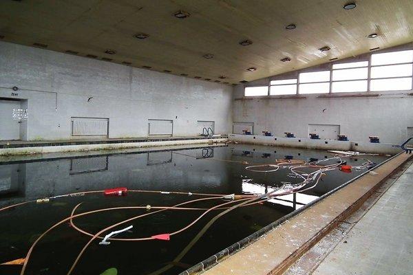 V bazéne je stále voda. Okrem nej je plný hadíc, dverí, odpadkov, kusov dreva, fliaš.