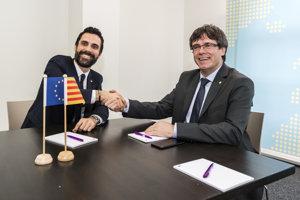 Predseda katalánskeho parlamentu Roger Torrent (vľavo) si podáva ruku s premiérom Carlesom Puigdemontom, ktorý je momentálne na úteku.