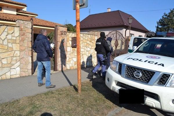 Polícia odvádza zadržaného muža z domu Rodovcov v Michalovciach.