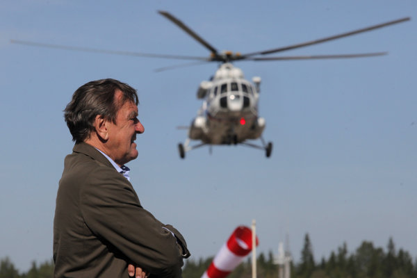 Nemecký expremiér Gerhard Schröder  čaká na príchod ruského premiéra Vladimíra Putina (v helikoptére) pred slávnostným napumpovaním plynu do plynovodu Severný prúd v zálive Portovaja 6.septembra 2011.