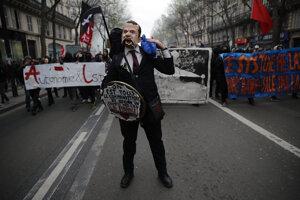Muž s maskou francúzskeho prezidenta Emmanuela Macrona počas demonštrácie.