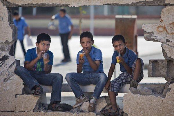 Palestínski chlapci popíjajú džús na poškodenom múre školy v Gaze.