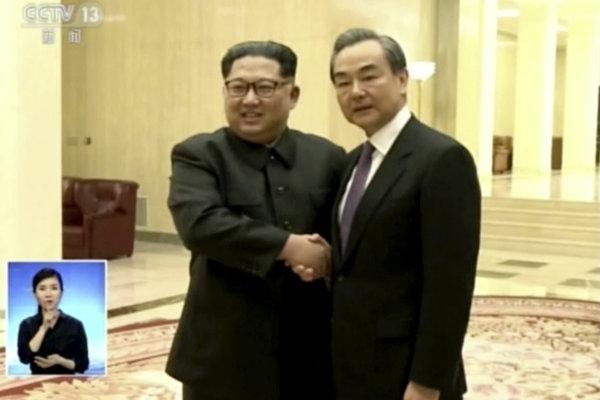 Severokórejský vodca Kim Čong-un (vľavo) so šéfom čínskej diplomacie Wangom I.